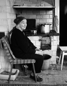 Woman sitting on front of a wood stove