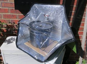 Solar oven in sun with 10 litre black bucket inside