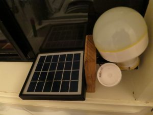 Battery powered lamp attached to small solar panel