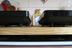 Portable induction hot plates resting on timber which is supported by unused gas stovetop