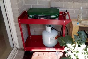 Outdoor stove and LPG bottle under a pergola
