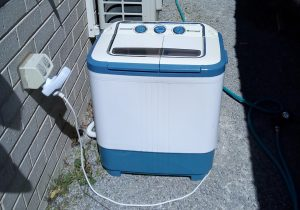 Portable washing machine plugged in with energy monitor
