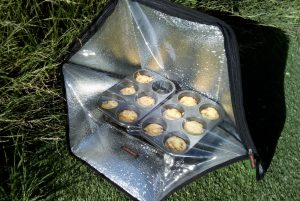 Solar oven in sun with muffin tray inside